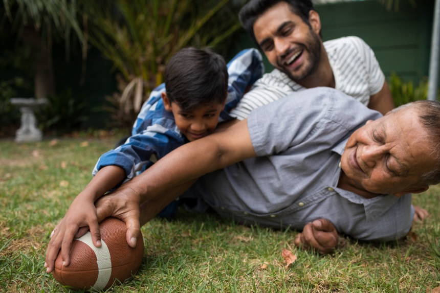 Happy family playing american football in yard
