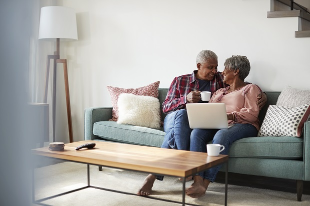 Senior Couple Sitting On Sofa At Home Using Laptop To Shop Online