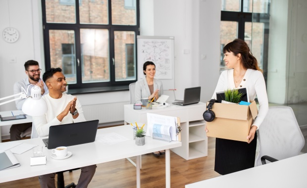 colleagues applauding to female office worker
