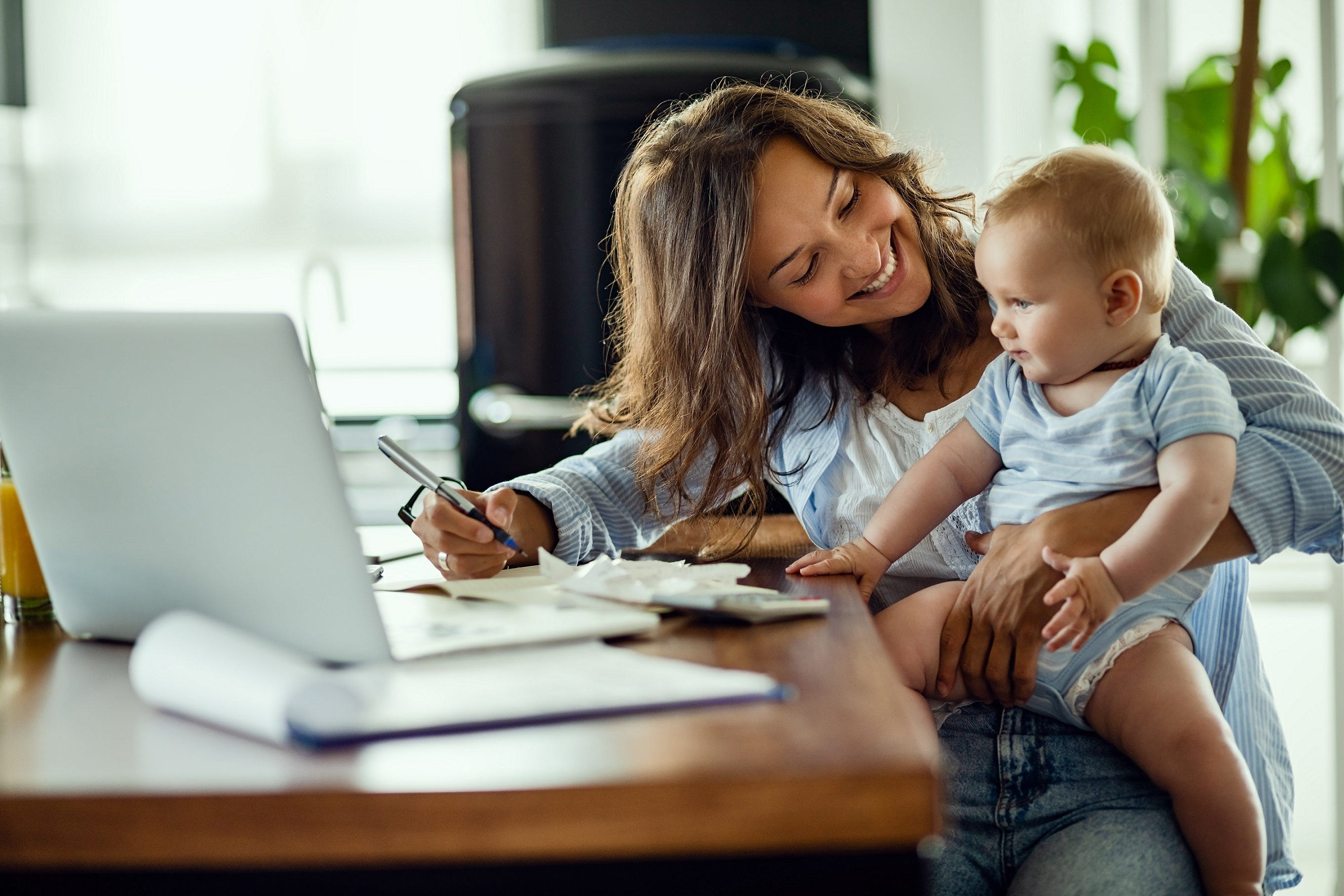 Happy mother talking to her baby while working at home.