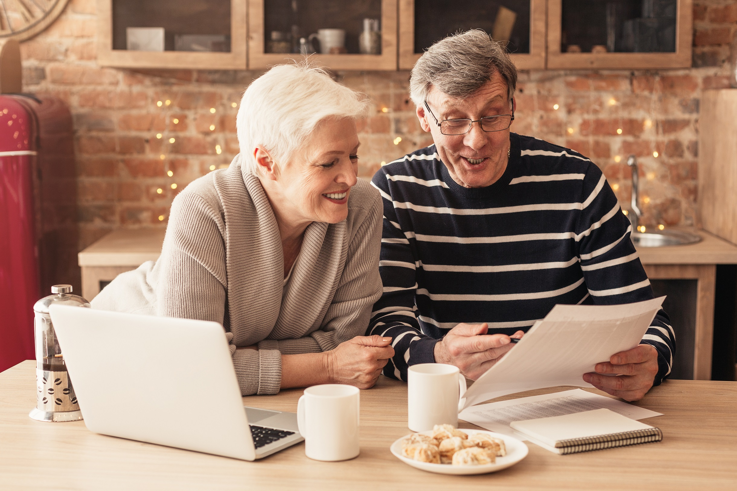 Smiling Senior Couple Reading Health Insurance Policy Contract In Kitchen Together