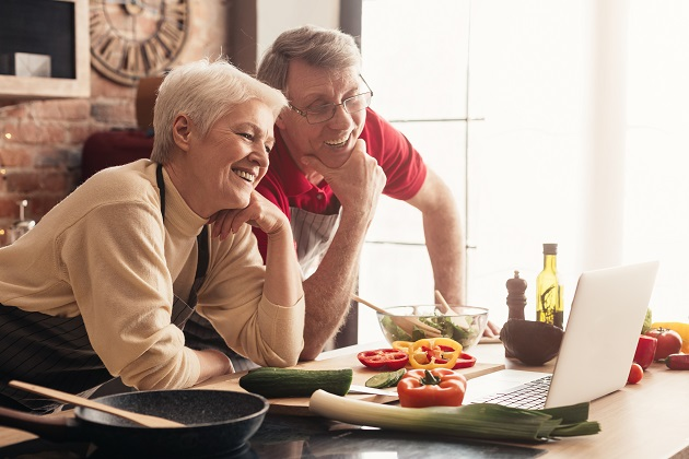 Cheerful Senior Couple Using Laptop In Kitchen, Watching Culinary Recipies Together
