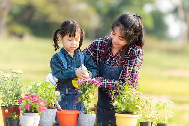 Family child girl helping mother care plant flower in garden. Young people mom and daughter gardening outdoor sunny nature background. Happy and enjoy in spring and summer day. Family Concept.